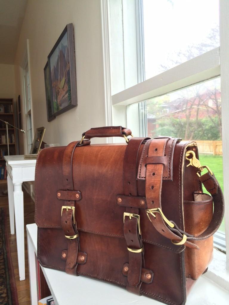 front/side view of dark brown sunburst handmade leather bag